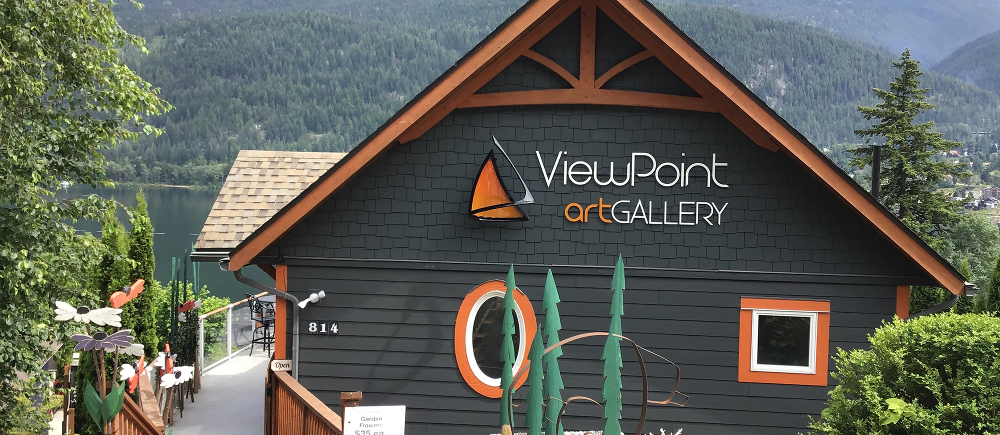 the Viewpoint Art Gallery building sitting above Kootenay Lake with mountains in the background
