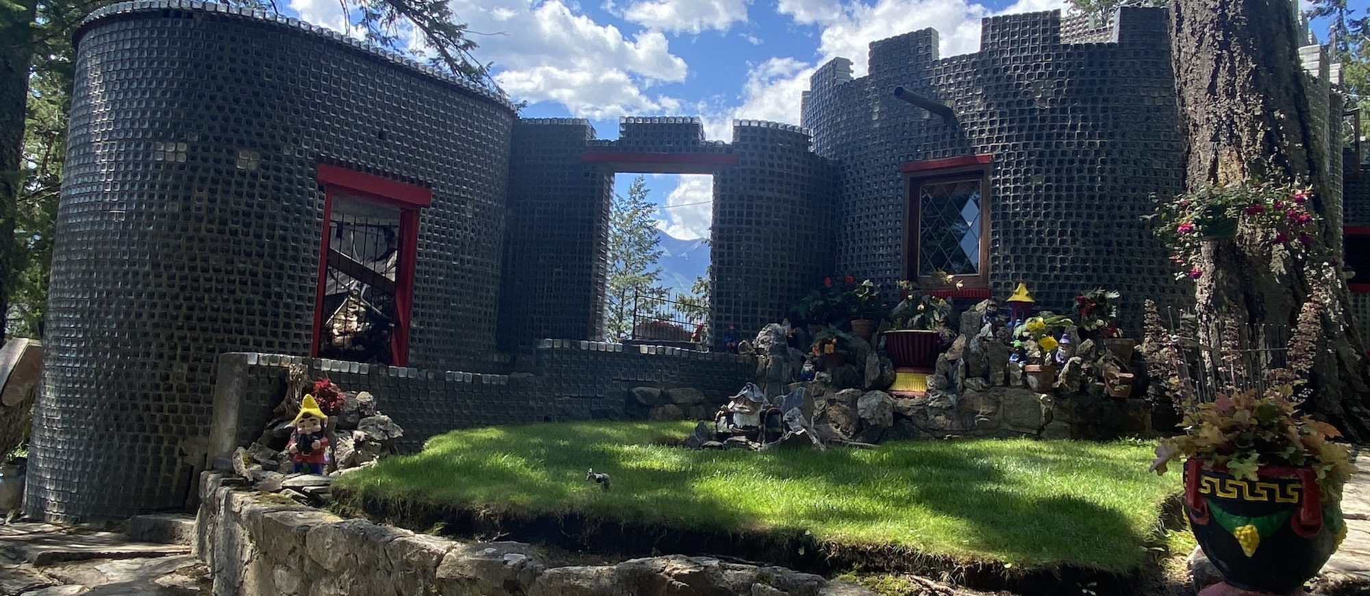A castle-like house made out of glass bottles with green grass and lawn gnomes around it.