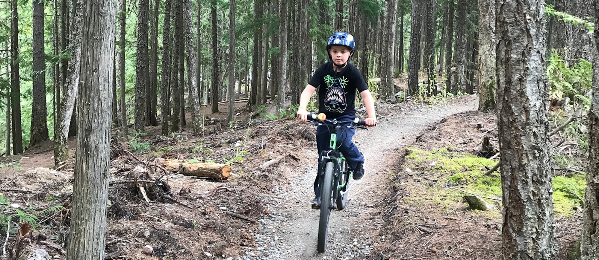 A boy riding his bike at the Kaslo Pump Track.