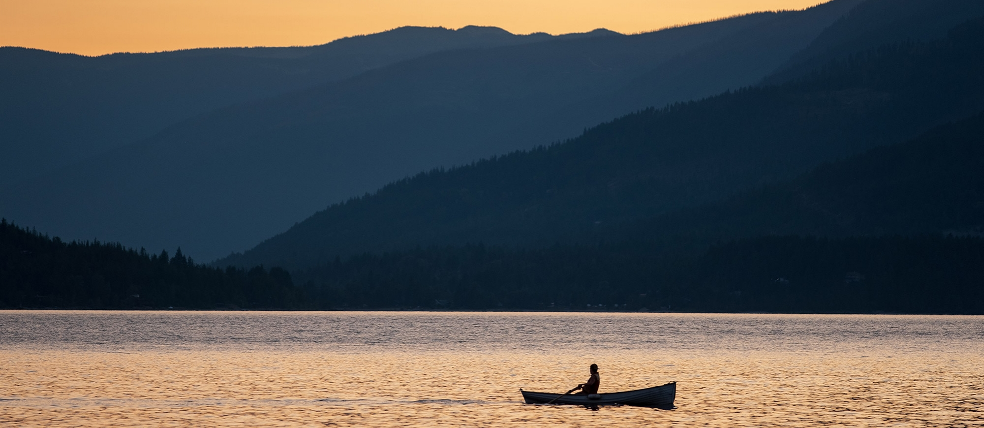 A person in a row boat silhouetted by the sunset on Kootenay Lake