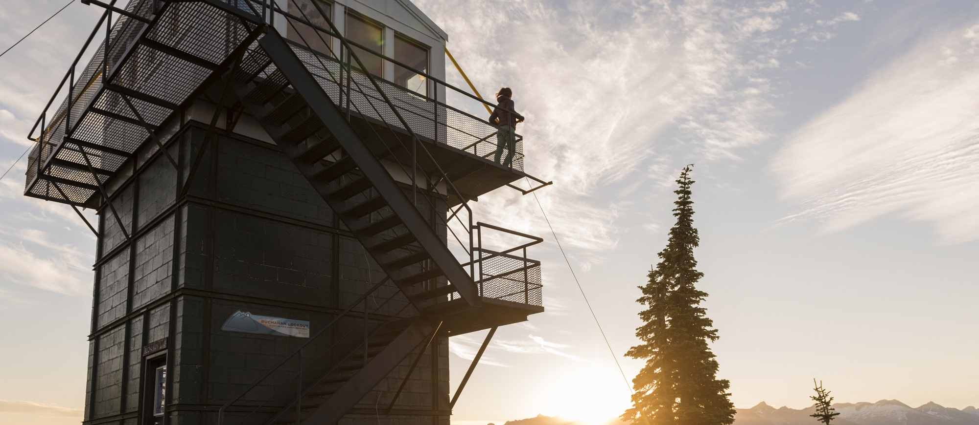 Someone standing on the balcony of the old fire watch tower on Mt Buchanan near Kaslo, BC