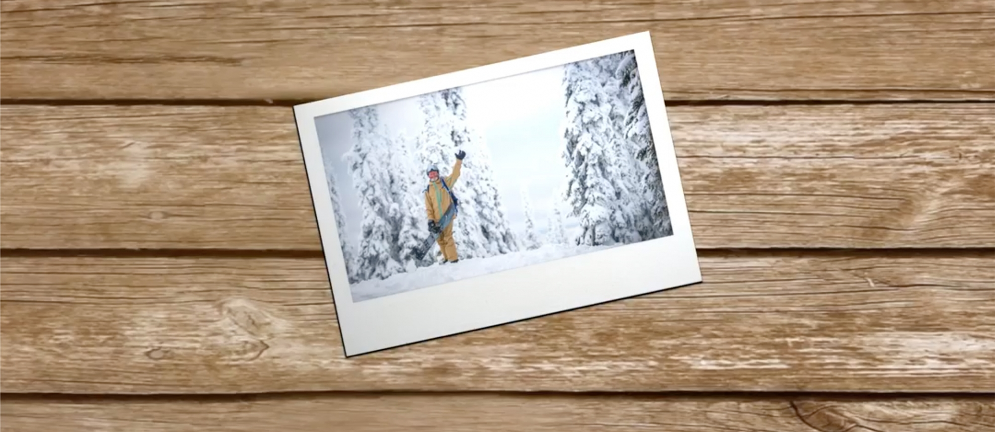 Photo lying on a wooden desk at an angle, of man on snowy day waving at camera
