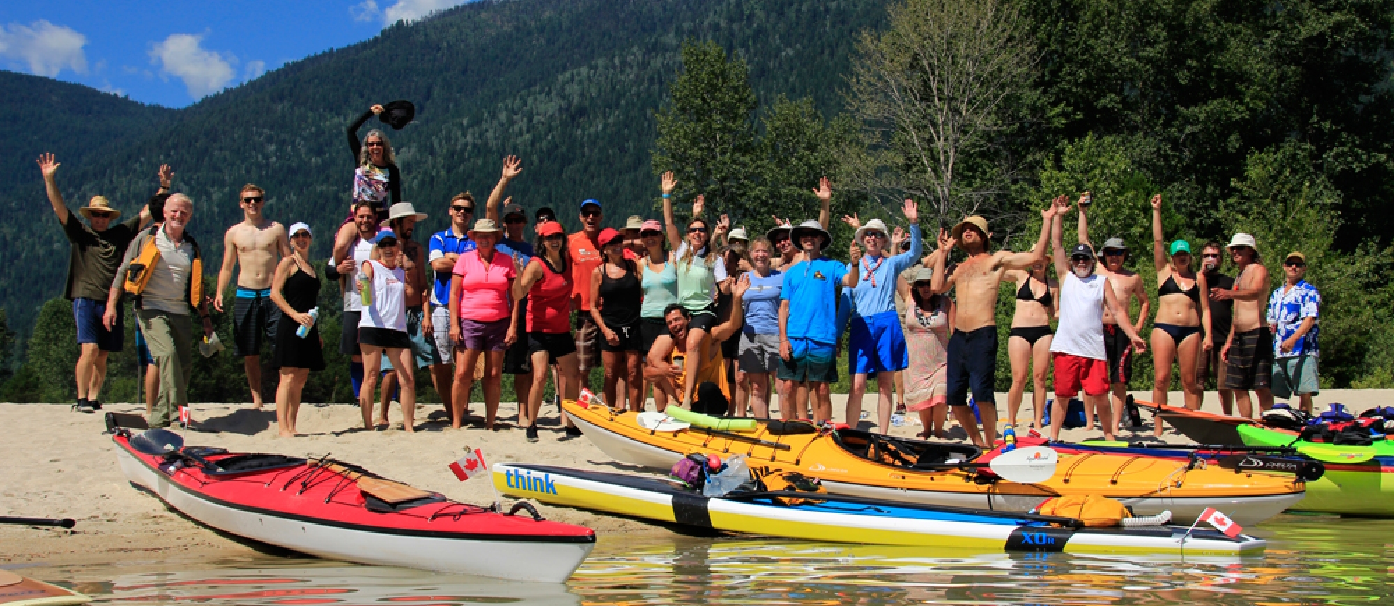 A large group of paddlers standing on the beach waving at Kokanee Creek Provincial Park