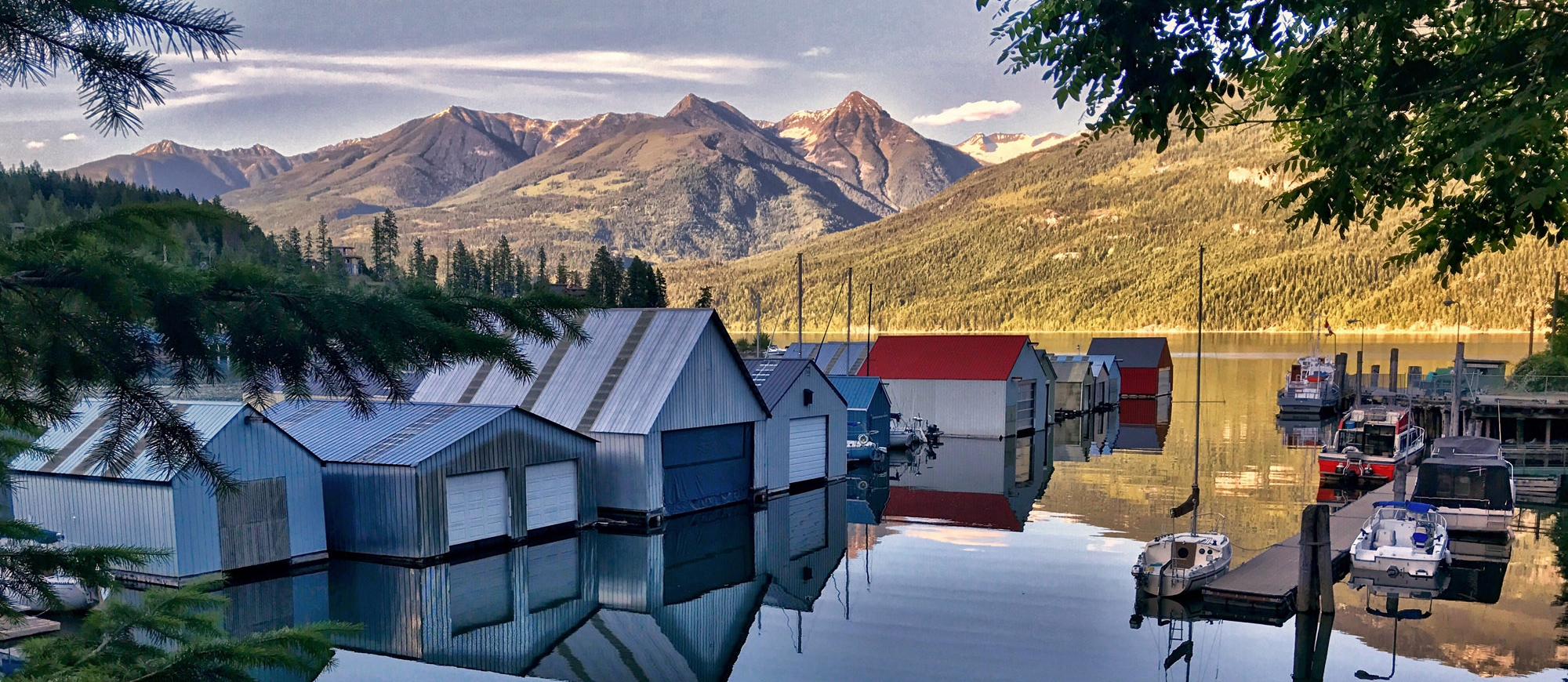 The boat houses in Kaslo BC with a very clear reflection in water and mountains in the background
