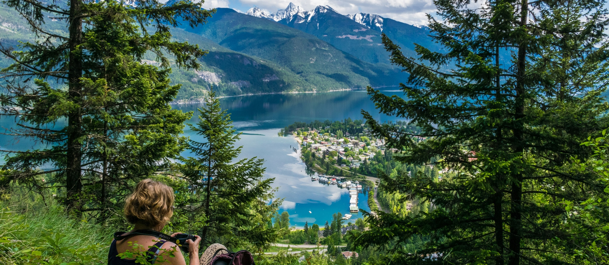 Woman with a camera sitting in the grass overlooking Kaslo, BC and Kootenay Lake