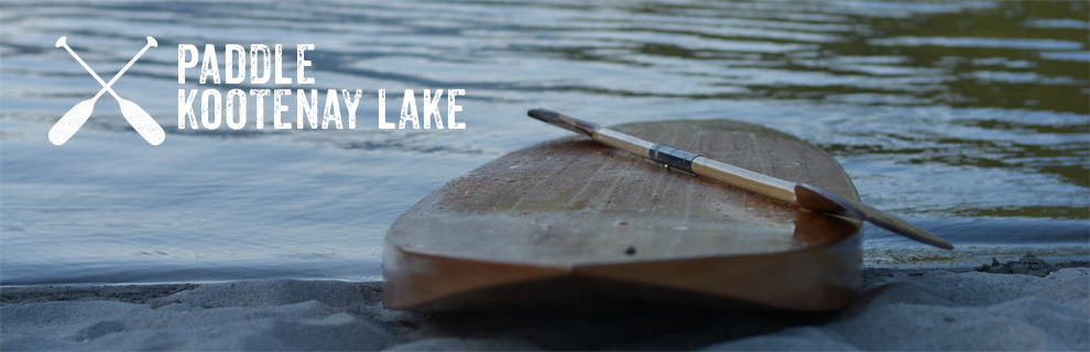 A handmade wood paddle board resting on the sand of Kootenay Lake.