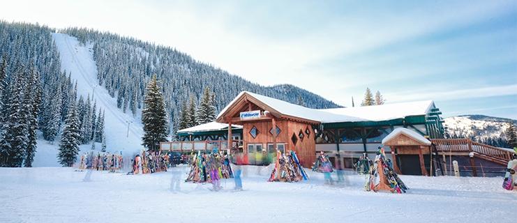 The lodge at Whitewater Ski Resort with people moving outside.
