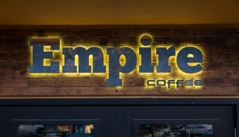 The Empire Coffee sign lit up on the outside of the building