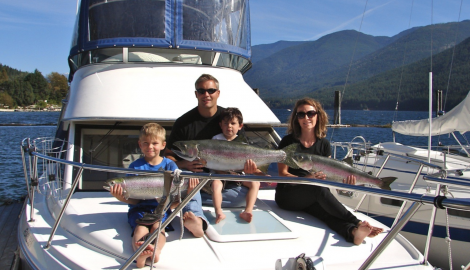 A mom, dad and two children hold up the fish they've caught on a Kootenay Wild Fishing Charter boat