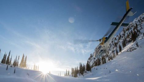 photo of a high terrain helicopter landing in the snow surrounded by mountains