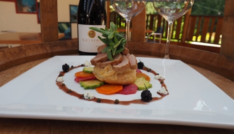 A plate of delicious looking food with two wine glasses and a bottle of red wine