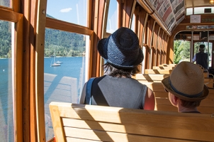 Mother and son looking out the window of Streetcar #23 to views of Kootenay Lake.